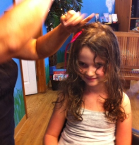 Photo of hair feather being put in girl's hair