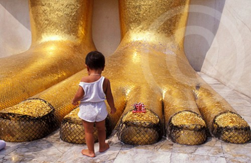 Photo of kid at the feet of a Buddha in Thailand