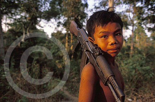 Photograph of a boy in Cambodia with an AK-47 gun