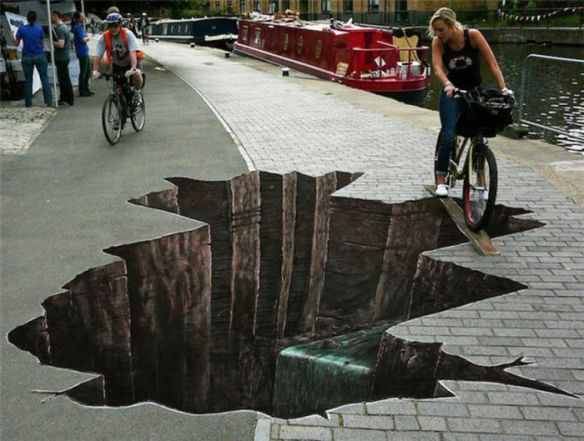 Photo of street art sink hole with bicylist