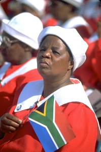 Photo of South African woman holding the new flag at a rally for Nelson Mandela