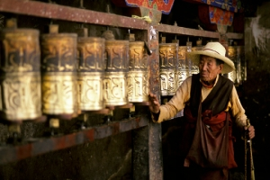 Tibetan pilgrim spinning prayer wheels in Lhasa, Tibet